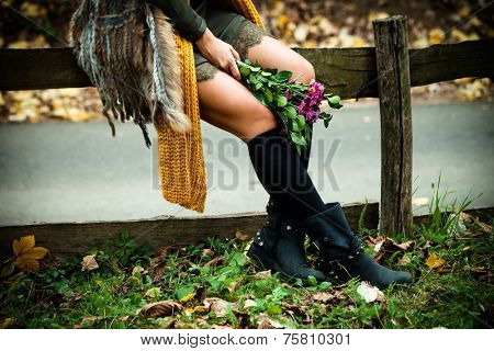 woman sit in park on wooden fence wearing leather boots, wool scarf, green dress hold in hand flowers