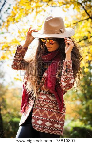 young woman with long curly hair wearing hat,  sunglasses, coat and  red scarf enjoy in autumn sunny day in park