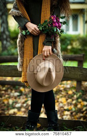 autumn fashion details, hat, wool scarf, fur vest and bouquet of flowers in her hand, woman stand in park near the wooden fence