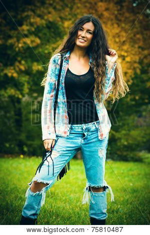smiling young woman with long curly hair in blue torn jeans and tartan shirt outdoor shot autumn day in park