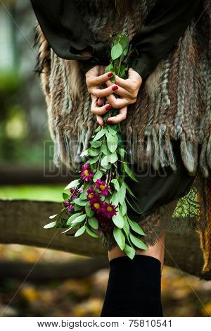 woman wearing long fur vest and green dress with hands holding flowers behind back outdoor shot in park