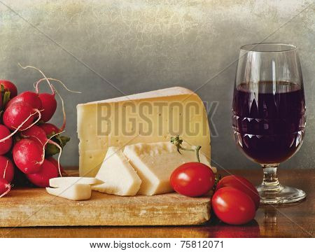 Italian Cheese Assortment With Vegetables And A Glass Of Red Wine