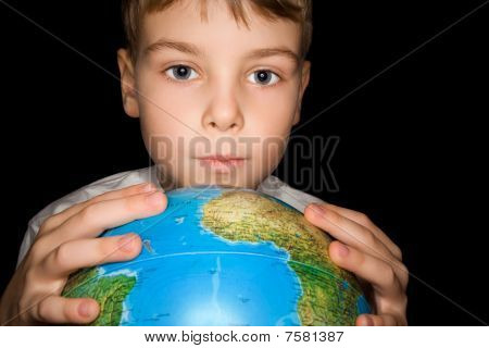 Boy Keeps In Hands Over Globe Of World Isolated On Black