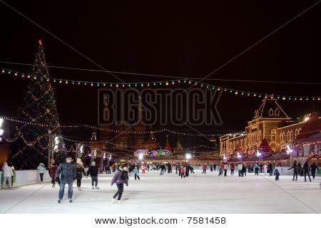 Pista de patinaje en la Plaza Roja en Moscú en la noche. Casa de comercio de la goma