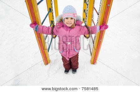 hübsch lächelnd mädchen in rosa Jacke auf Spielplatz, winter