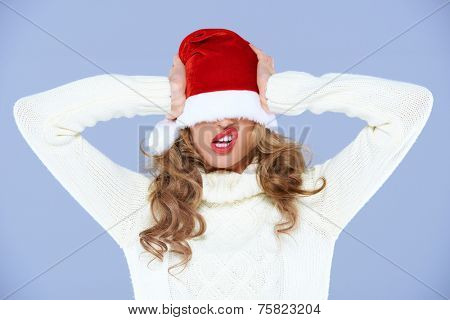 Young woman in an oversized Santa hat which is covering her eyes pulling a funny face as she tries to wrest it off with her hands while celebrating Christmas