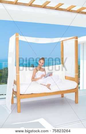 Elegant happy woman sitting on a canopied day bed on an outdoor tropical patio smiling at the camera