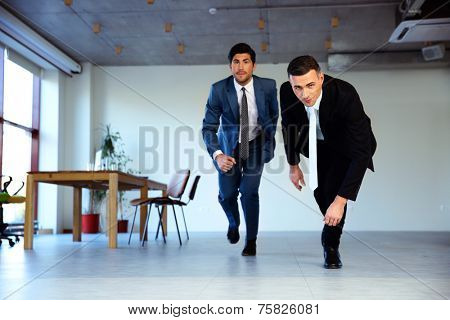 Two businessman running together in office. Business concept