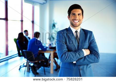 Cheerful businessman standing with arms folded in front of colleagues