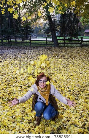 Young Caucasian Woman Throwing Yellow Leaves
