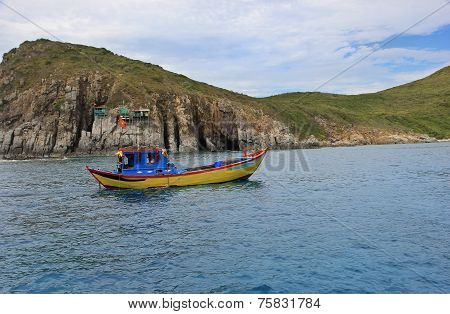 Boat At Sea On A Background Of Rocks