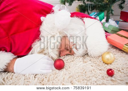 Exhausted santa resting on the rug near gifts and christmas tree
