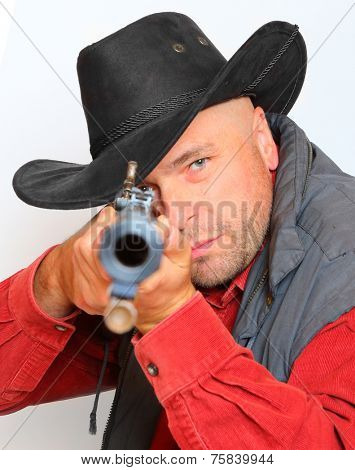 Cowboy with big bore rifle aimed at you. Legal defense and gun control concept.