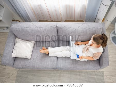 Young Housewife Laying On Sofa In Living Room And Making Online Shopping