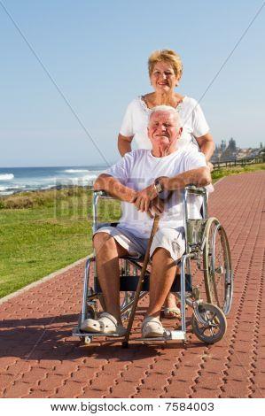 caring senior wife pushing happy husband in wheelchair