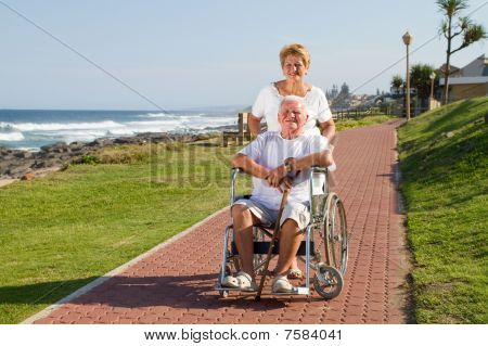 happy senior wife pushing elderly husband in wheelchair
