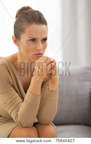 Concerned Young Housewife Sitting In Living Room
