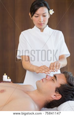 Side view of a handsome young man receiving treatment at spa center