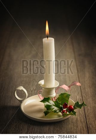 Lit candle in chamberstick with holly and berries for Christmas decoration