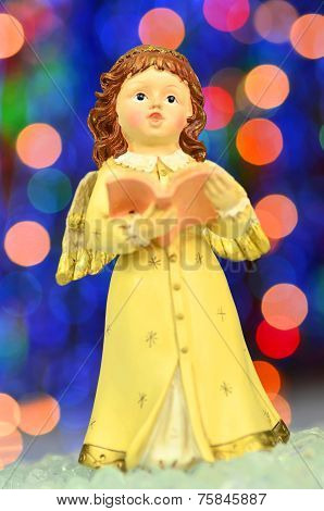 Christmas decoration, figure of little angel singing carols against bokeh background