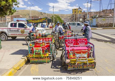 PUNO, PERU, MAY 5, 2014: Pedicabs drivers wait for tourists and local passengers near the port
