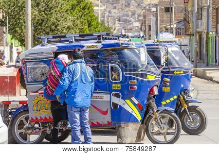 PUNO, PERU, MAY 5, 2014: Local couple enters an auto rickshaw waiting on street