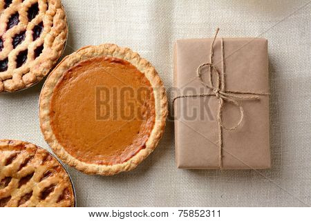 High angle shot of three holiday pies and a wrapped parcel on a burlap tablecloth. The cherry and apple pies run out of the frame with a whole pumpkin pie and package dominate the frame.