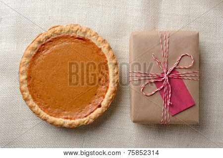 High angle shot of a holiday pumpkin pie and plain paper wrapped present. The brown gift is tied with red and white string and has a red gift tag. Horizontal format.