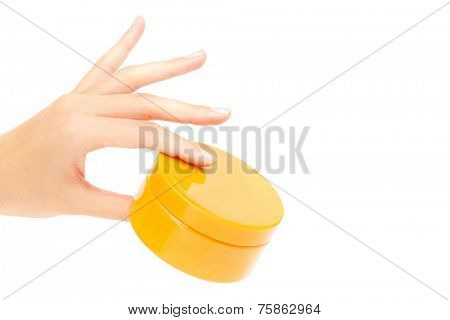 Female hand holding container with cream or scrub in isolation