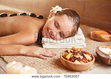 Peaceful woman relaxing in spa salon with her head on folded soft towel and hot stones on her back
