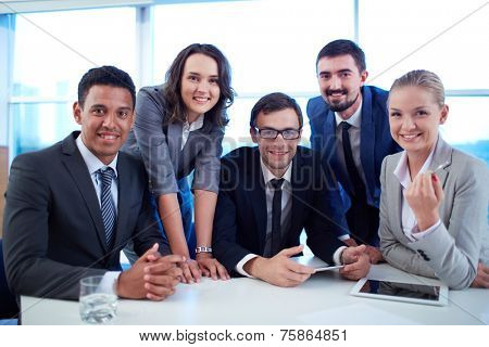 Group of successful business partners looking at camera at meeting