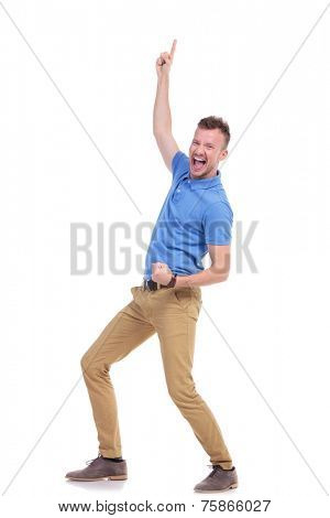 full length picture of a young casual man cheering and pointing upward while smiling for the camera. isolated on a white background