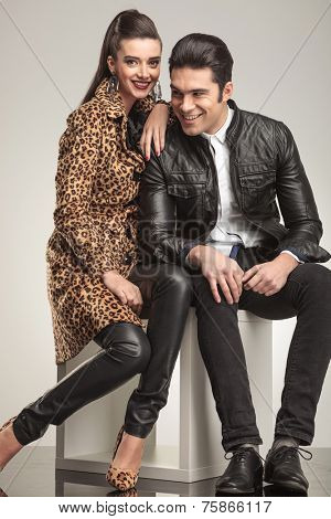 Cute fashion couple smiling while sitting on a white cube, the woman is looking at the camera while the man si looking away.