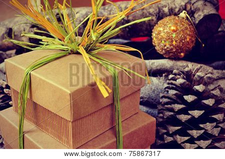 some gift boxes tied with natural raffia of different colors with christmas balls, pinecones and logs in the background