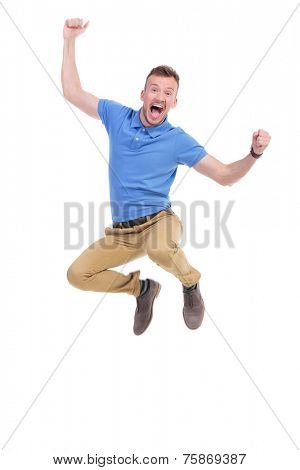 casual young man cheering while jumping in the air. isolated on white