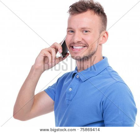 close up portrait of a young casual man making a call while smiling for the camera. isolated on a white background