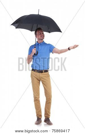 full length picture of a young casual man holding an umbrella and reaching a hand into the rain while looking at it. isolated on a white background