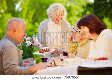Happy group of senior people eating ring cake at birthday party in a garden