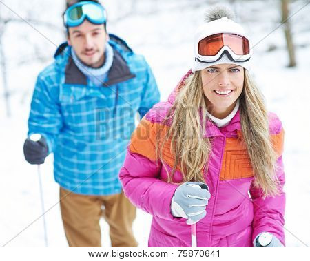 Happy couple in winter doing hiking trip with ski poles