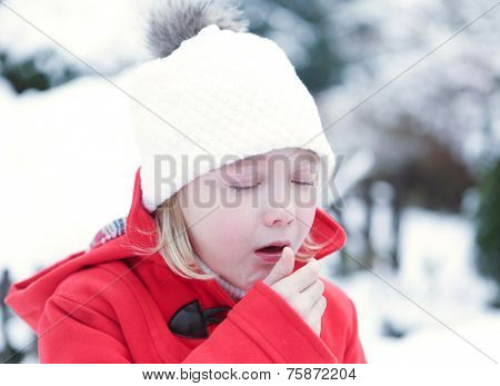 Sick girl coughing with flu in a snowy winter