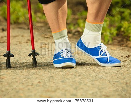 Active Senior Legs In Sneakers Nordic Walking In A Park.