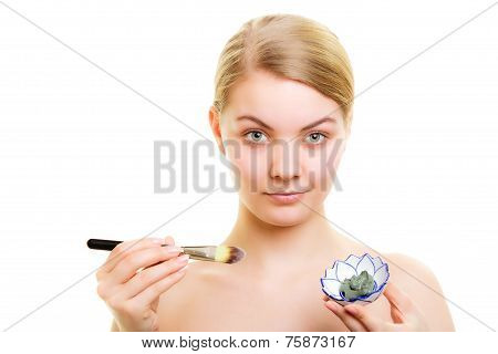 Skin Care. Woman Applying Clay Mud Mask On Face.