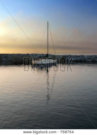 Sailboat in harbor at sundown