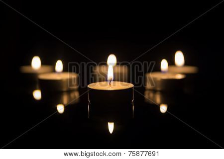 Tea Candles with Reflection on Black