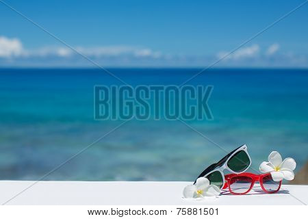 Two pair of sun glasses on a beach table on blue ocean background