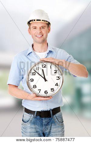 Businessman wearing helmet holding a clock