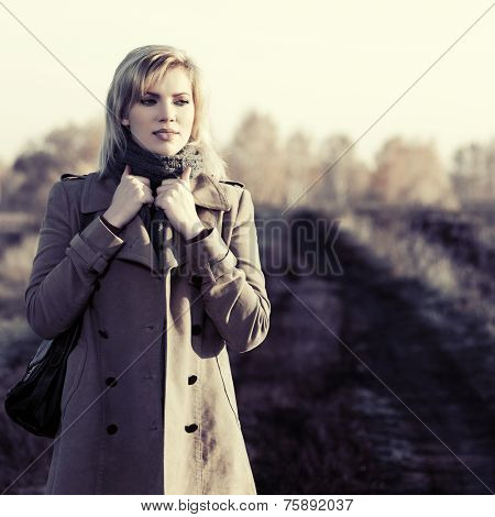 Happy young blond fashion woman walking in autumn field