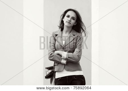 Young fashion woman with handbag standing at the wall