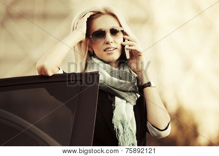 Fashion business woman calling on mobile phone at the car