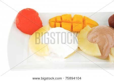 tropical fruits and ice cream on white plate